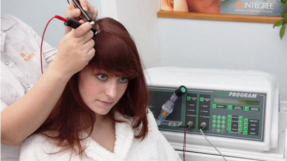 Девушке делают физиопроцедуру на кожу головы
