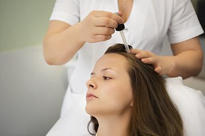 девушке делают процедуры по лечению волос